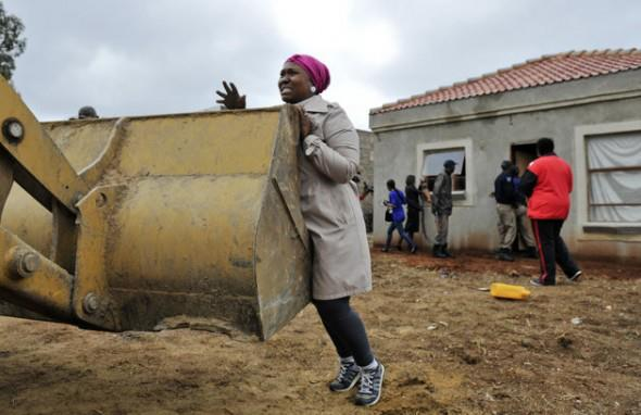 A woman trying to stop her  house from being Demolished in Lenasia, South of Johannesburg