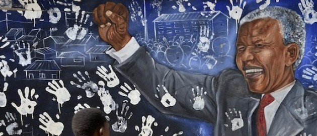 A boy walks past a mural painted outside former President Nelson Mandela's former home in Alexandra Township. Pic. Reuters/Mujahid Safodien.